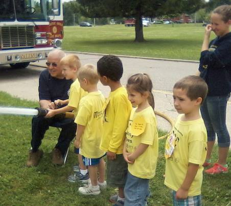 fireman showing students a water hose