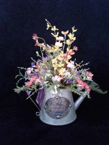 Rife's large tin watering can full of Spring flowers and grasses.