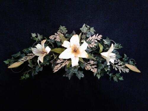 Rife's hanging metal arch decorated with cream-colored lilies and ivy.