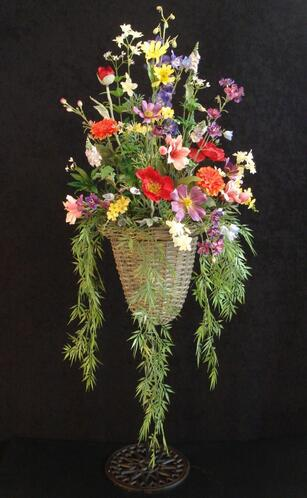 Rife's hanging wicker basket filled with summery flowers and trailing ivy.