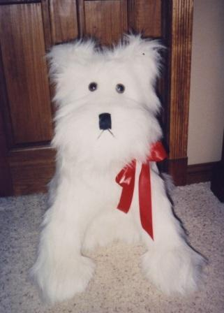 Conrad's white sitting dog, made of white shaggy fur fabric, safety lock eyes, stuffed with polyester stuffing.