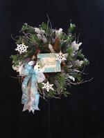 "Rife's wintry ""welcome"" twig wreath adorned with white snowflakes, pine cones and evergreen."