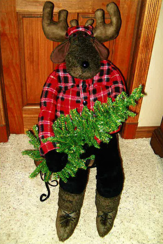 Conrad's sitting moose made with fur & fleece fabric, safety lock eyes and has a removable Christmas tree.  Stuffed with polyester stuffing.