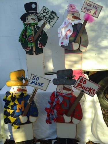 Youtsey handpainted wooden snowmen holding college signs.